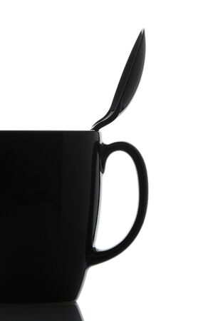 Close up of a black coffee mug with spoon over a white background. Spoon is inside cup leaning on the handle side. Vertical format with copy space. Stock Photo - 7753947