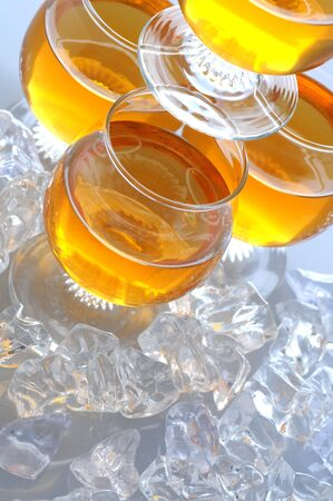 BARWARE: Stacked Cocktails with ice cubes on table, vertical format at a slant Stock Photo
