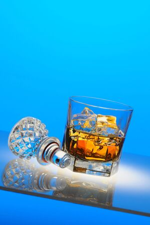 Glass of scotch on the rocks with decanter stopper and reflections. Vertical composition at a slant with copy space over white background. photo