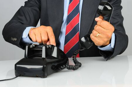 Close up of a businessman dialing an old fashioned rotary telephone. Horizontal format showing phone, hand and torso only. photo