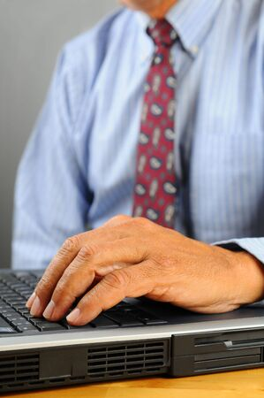 Close up of a businessman hands and laptop computer with torso out of focus. Vertical Format with shallow depth of field. Stock Photo - 7886537
