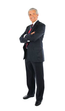 Smiling middle aged businessman in a suit and tie standing with his arms folded. Full length over a white background.