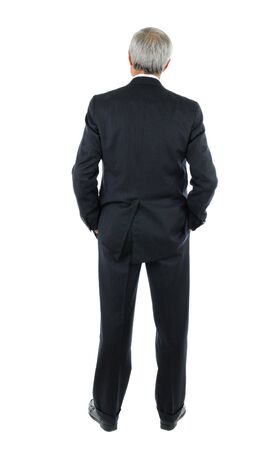 Standing middle aged businessman with both hands in his pockets. Full length shot of the mans back over a white background. photo