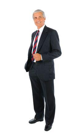 중간 웃 고 사업가 양복과 그의 주머니에 한 손으로 서 넥타이 세. 흰색 배경 위에 전체 길이입니다.