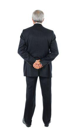 Debout entrepreneur moyen âge avec les deux mains derrière le dos. Pleine longueur grenaille du mans sur un fond blanc.