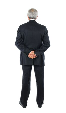 people from behind: Standing middle aged businessman with both hands behind his back. Full length shot of the mans back over a white background. Stock Photo