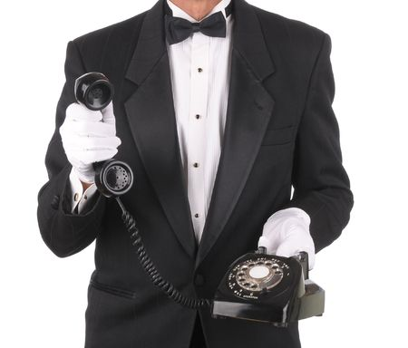 Butler Holding an Old Rotary Telephone with the receiver in one hand isolated on white torso only. photo