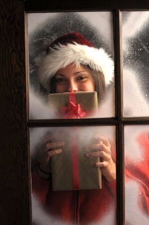 composition vertical: Sorridente Teenage ragazza nella finestra ricoperto di gelo detiene un Natale presente davanti alla sua composizione verticale del viso Archivio Fotografico