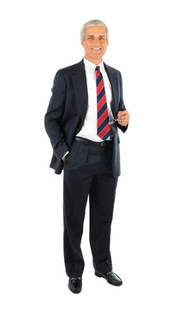 old man standing: Smiling middle aged businessman wearing a suit standing with one hand in his pocket and the other holding his eye glasses. Full length over a white background. Stock Photo
