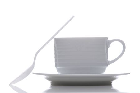 White china coffee cup and saucer with plastic spoon resting against the side of the cup. Stock Photo - 8094205