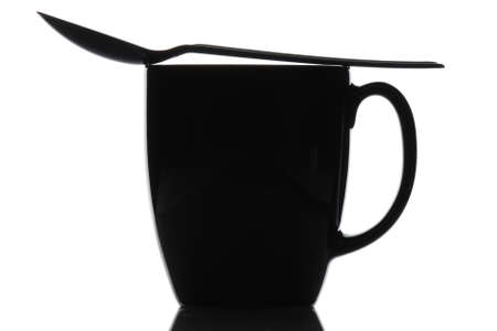 Close up of a black coffee mug with spoon over a white background. Spoon is laying across the top of the cup. Horizontal format. Stock Photo - 8094203