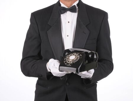 Butler in Tuxedo holding an old rotary telephone in front of his body. Torso shot only isolated over a white background. photo