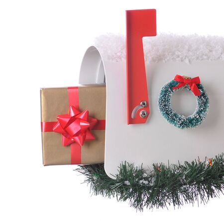 Christmas package sticking out of and open Mailbox decorated for the holidays isolated on white. Square Composition Stock Photo