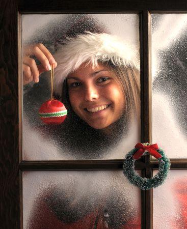 glasscheibe: Smiling Teenage Girl in Fenster bedeckt mit Frost holding a Christmas Ornament an Ihr Gesicht vertikale Zusammensetzung