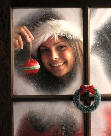 frost covered: Smiling Teenage girl in window covered with frost holding a Christmas Ornament in front of her face vertical composition
