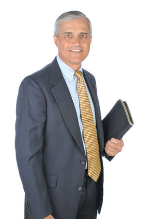 Middle aged businessman holding notebook in one hand. Man is standing and smiling. Vertical format isolated on white. Archivio Fotografico