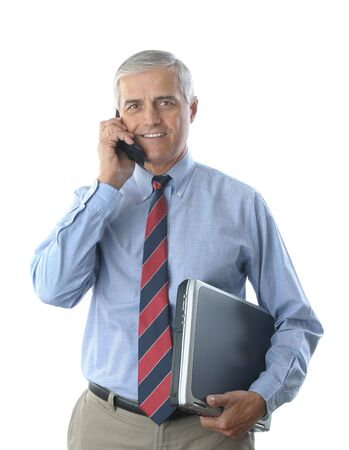 khaki pants: Smiling middle aged businessman talking on a cell phone, and holding a laptop computer under his other arm. Vertical format isolated on white.  Stock Photo
