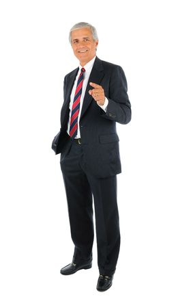 Smiling middle aged businessman standing and pointing with one hand and the other hand in his pocket. Full length over a white background. photo