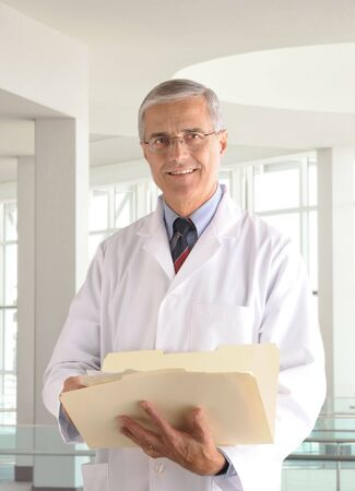 50 yrs: Middle aged male doctor in lab coat holding a manila folder in modern medical office setting.  Stock Photo