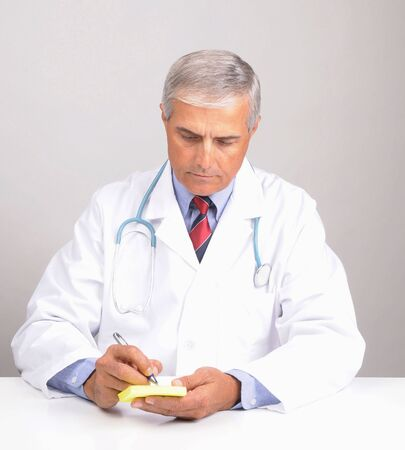 50 yrs: Middle aged male doctor in lab coat with stethoscope writing on a  Prescription Pad