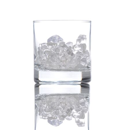 barware: Glass partially filled with ice cubes, isolated over white with reflection.