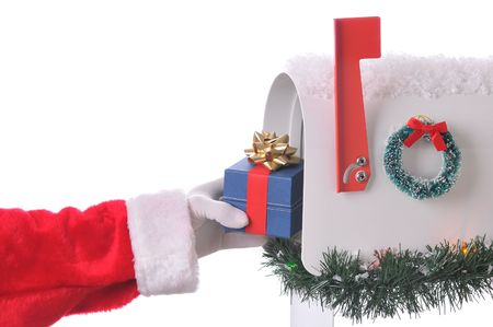 postbox: Santa Claus placing a Christmas present into an open Mailbox decorated for the holidays isolated on white. Horizontal composition with only hand and arm visible. Stock Photo