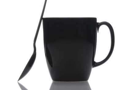 Close up of a black coffee mug with spoon over a white background. Spoon is leaning against the side of the cup. Horizontal format.