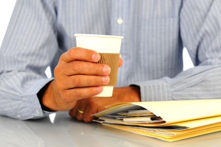 Businessman leaning on desk and a stack of work files holding a coffee cup in one hand,. Shallow depth of field with focus on hand and cup. Horizontal format. Stock Photo - 8176465