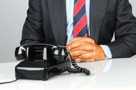 rotary phone: Businessman sitting at his desk with retro telephone waiting for a call. Close up shot of torso and desk only. Man has his hands together on des in front of phone. Horizontal format.