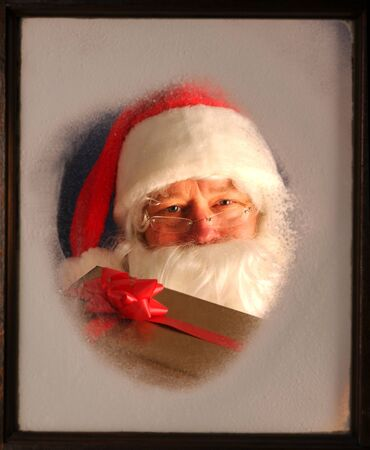Santa Claus seen through a frosted window holding up a wrapped present. photo