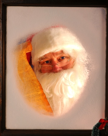 naughty or nice: Santa Claus seen through a frosted window holding up a scroll of his naughty and nice list.