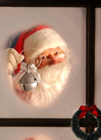 Santa Claus seen through a frosted window holding up a silver bell. photo