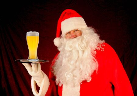 Santa Claus holding a serving tray with a large glass of beer. Horizontal format photo