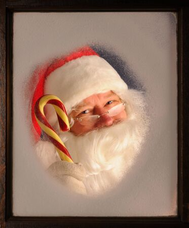 Santa Claus seen through a frosted window holding up a large candy cane. Stock Photo - 8257790