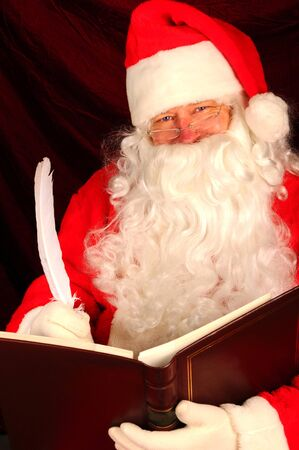 christmas costume: Close up of Santa Claus writing with a quill pen in a large leather bound book. Vertical format Stock Photo