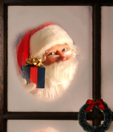 Santa Claus seen through a frosted window holding up a wrapped present. Stock Photo - 8257798