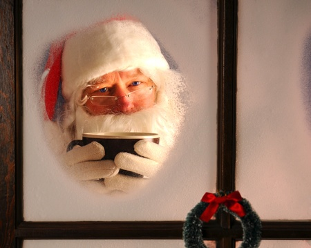 Santa Claus seen through a frosted window holding a large mug of cocoa. Horizontal format. photo