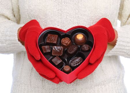Woman wearing red gloves and white sweater holding a Box Heart of Valentines Day Candy in front of her torso. Close shot in horizontal format.