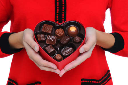 Woman wearing red sweater holding a Box Heart of Valentines Day Candy in front of her torso. Close shot in horizontal format. Stock Photo - 8552873
