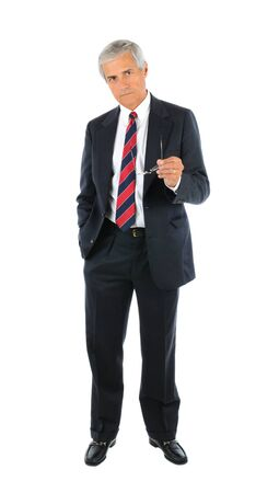 Serious middle aged businessman in a suit and tie standing with one hand in pocket and pointing with his glasses in opposite hand. Full length over a white background.
