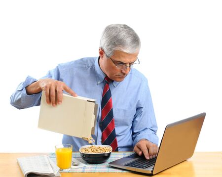 Middle aged man pouring his breakfast cereal into bowl. He is is busy working on his laptop computer and not paying atention to what he is doing. Horizontal format isolated over white. photo