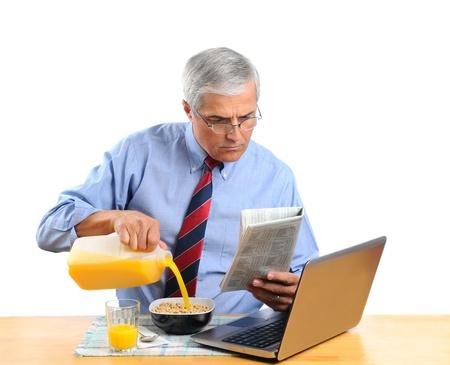 comiendo cereal: Media de a�os hombre verter el jugo de naranja en su insead de taz�n de cereal de desayuno de leche. Es de su ordenador port�til, leyendo el peri�dico de la ma�ana. Formato horizontal aislado en blanco. Foto de archivo