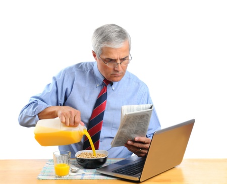 cereal bowl: Middle aged man pouring Orange Juice into his breakfast cereal bowl insead of milk . He is in front of his laptop computer reading the morning newspaper. Horizontal format isolated over white. Stock Photo
