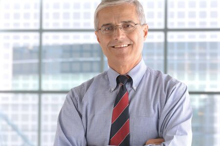 50 yrs: Close up of a smiling middle aged businessman in the lobby of a modern office building. Man is standing in front of a large window wearing a blue shirt and necktie. Horizontal Format.
