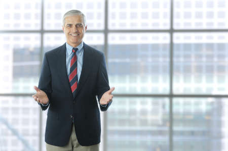 50 yrs: Smiling middle aged businessman standing in the lobby of a modern office building. Man is wearing a blue blazer and khaki pants and gesturing with both hands. Horizontal Format.