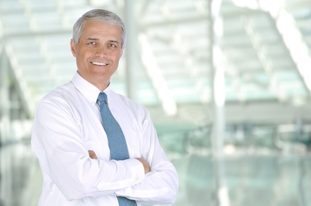 old man standing: Smiling middle aged businessman standing in the lobby of a modern office building. Man is wearing white shirt and necktie with his arms crossed. Horizontal Format. Stock Photo