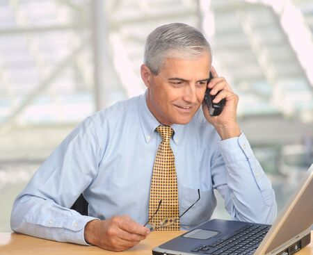 candid: Middle aged businessman with laptop talking on telephone in modern office setting. Square format. Stock Photo