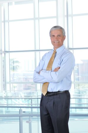Smiling middle aged businessman in a shirt and tie standing in a modern office building with his arms crossed. Vertical Format photo