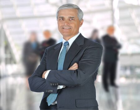 Smiling middle aged businessman in a suit and tie standing in a modern office building with his arms crossed in front of out of focus team. Square Format photo