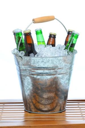 Bier emmer gevuld met diverse flessen en ijsblokjes op teak tafel voor een witte achtergrond.